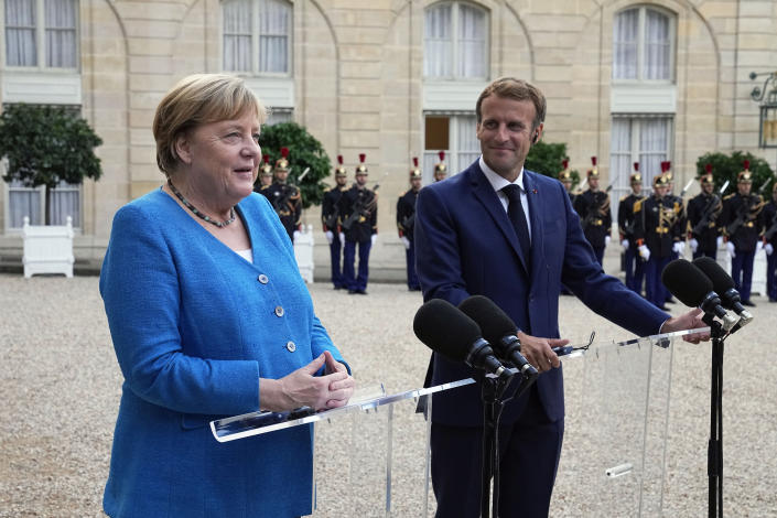 France's President Emmanuel Macron, right, and German Chancellor Angela Merkel give a press conference prior to a meeting at the Elysee Palace, in Paris, Thursday, Sept. 16, 2021. (AP Photo/Michel Euler)
