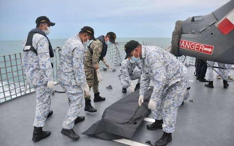 Navy sailors cover an unidentified body on to the deck of KD Lekiu frigate after it was recovered in the waters off the Johor coast of Malaysia - Credit: AP