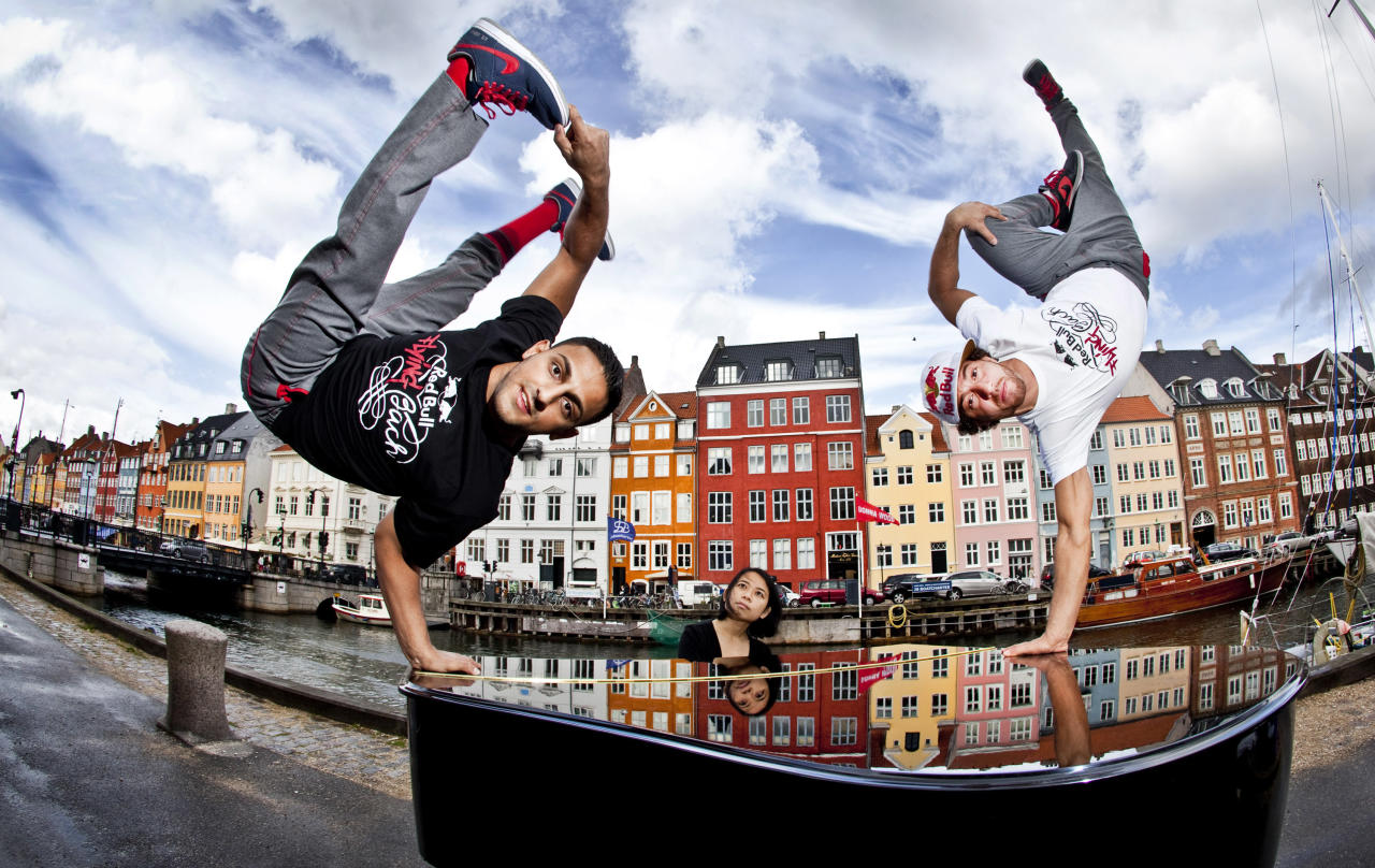 "In this handout image provided by Red Bull, Gengis ""Lil Ceng"" Ademoski (L) and Khaled ""KC"" Chaabi (R) of the four time world champion Berlin dance troupe ""Flying Steps"" strike a freeze on a piano played by muscian Jia Lim (C) of Singapore at the 17th century waterfront area of Nyhavn in build up to the Red Bull Flying Bach European Tour, a show that features the cultural clash of break dancing with the classical music of Johann Sebastian Bach, on August 30, 2011 in Copenhagen, Denmark.  (Photo by Dean Treml/Red Bull via Getty Images)"