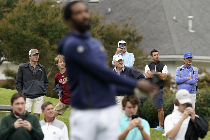 Fans watch as North Carolina A&T's J.R. Smith hits a tee shot on the first hole during the first round of the Phoenix Invitational golf tournament in Burlington, N.C., Monday, Oct. 11, 2021. Smith, who spent 16 years in the NBA made his college golfing debut in the tournament hosted by Elon. (AP Photo/Gerry Broome)