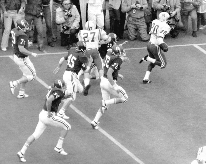 """FILE - In this Thanksgiving Day 1971 file photo, Nebraska's Johnny Rodgers (20) returns a punt for a touchdown as teammate Joe Blahak (27) delivers a block in the first quarter of an NCAA college football game against Oklahoma, in Norman, Okla. The game, which Nebraska won 35-31, is widely remembered as """"The Game of the Century."""" Fifty years later, Rodgers still gets asked about the play. (Bob Gorham/Lincoln Journal Star via AP, File)"""