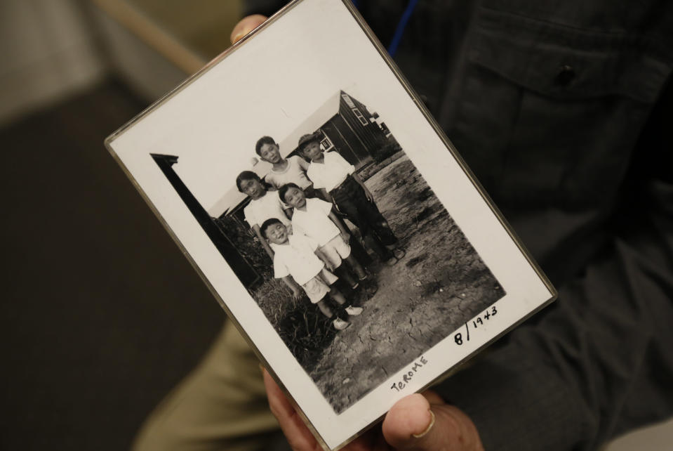 "In this photo taken Tuesday, Feb. 11, 2020, Les Ouchida holds a 1943 photo of himself, front row, center, and his siblings taken at the internment camp his family was moved to, as he poses at the permanent exhibit titled ""UpRooted Japanese Americans in World War II"" at the California Museum in Sacramento, Calif. Ochida, who is a docent for the exhibit, and his family were forced to move in 1942 from their home near Sacramento to a camp in Jerome, Arkansas. Assemblyman Al Muratsuchi, D-Torrence has introduced a resolution to apologize for the state's role in carrying out the federal government's internment of Japanese-Americans. A similar resolution will be brought up before the state Senate by Sen. Richard Pan, D-Sacramento. (AP Photo/Rich Pedroncelli)"