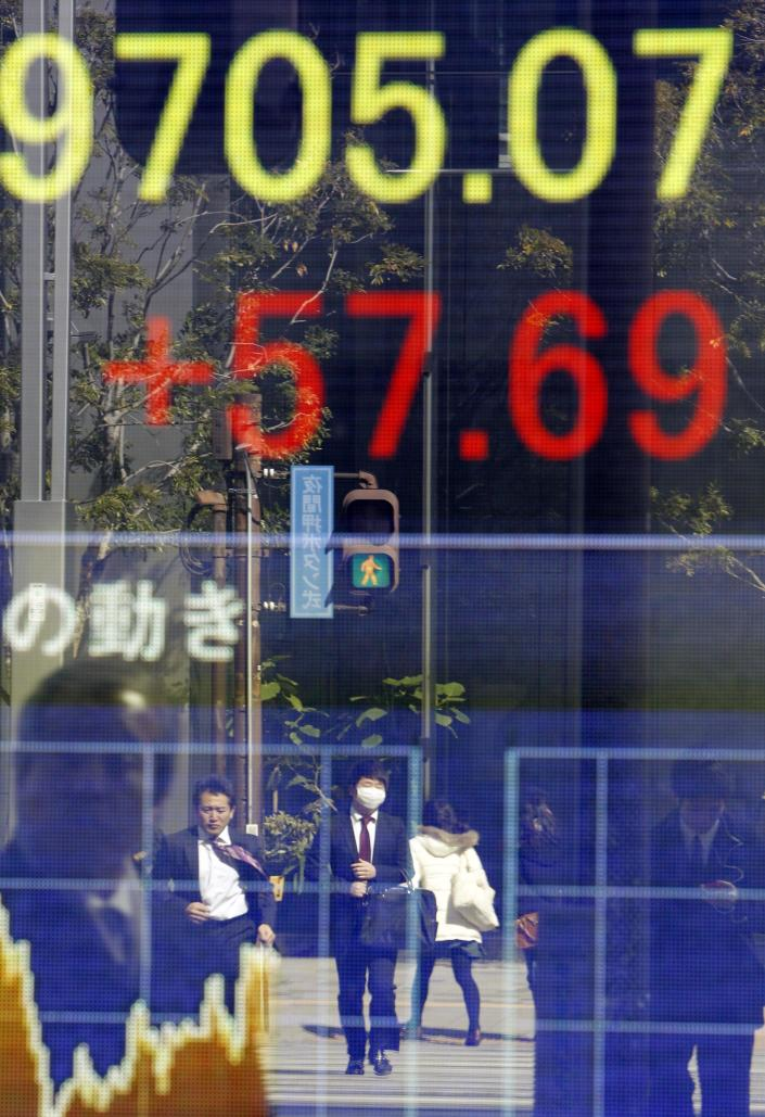 Passers-by are reflected on an electric stock board of a securities firm in Tokyo, Monday, Feb. 27, 2012. Japan's Nikkei 225 index rose to 9,705.07 during morning trading. Asian stock markets were mostly higher Monday as investors looked ahead to data releases that analysts say will likely show the U.S. economy improving at a slow but steady clip. (AP Photo/Koji Sasahara)
