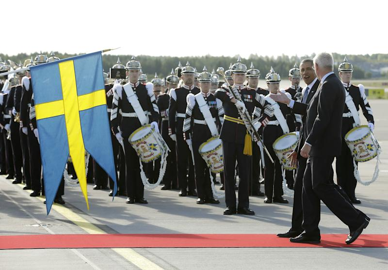 CORRECTS THE IDENTITY OF THE PERSON ACCOMPANYING OBAMA U.S. President Barack Obama walks with Sweden's Foreign Minister Carl Bildt, right, past members of the Royal Life Guards: Honorary Guard and Colour Guard, during the arrival ceremony at Stockholm-Arlanda International Airport, Wednesday, Sept. 4, 2013, in Stockholm, Sweden. (AP Photo/Pablo Martinez Monsivais)