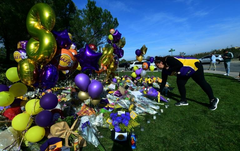 A Lakers fan lays flowers at a makeshift memorial outside the gated community to the late NBA great Kobe Bryant's home