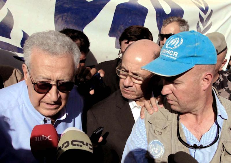 Lakhdar Brahimi, the U.N.-Arab League envoy to Syria, left, speaks to reporters, as UNHCR representative to Jordan, Andrew Harper, right, listens during his visit to the Zaatari Refugees Camp for Syrians who fled the civil war in their country in Mafraq, Jordan, Tuesday, Sept. 18, 2012. (AP Photo/Raad Adayleh)