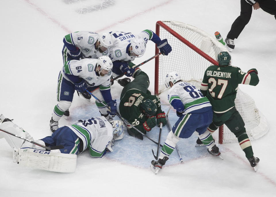Vancouver Canucks goalie Jacob Markstrom (25) makes the save as the Vancouver Canucks and the Minnesota Wild scramble in the crease during the second period of an NHL hockey playoff game Thursday, Aug. 6, 2020 in Edmonton, Alberta. (Jason Franson/The Canadian Press via AP)