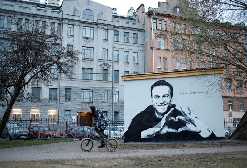 A person rides a bicycle past a graffiti depicting Alexei Navalny in Saint Petersburg