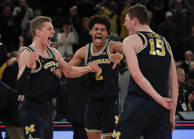 "From left, Michigan forward <a class=""link rapid-noclick-resp"" href=""/ncaab/players/131251/"" data-ylk=""slk:Moritz Wagner"">Moritz Wagner</a>, guard Jordan Poole (2) and center Jon Teske (15) celebrate after Michigan beat Purdue of the NCAA Big Ten Conference tournament championship college basketball game, Sunday, March 4, 2018, in New York. Michigan won 75-66. (AP Photo/Julie Jacobson)"