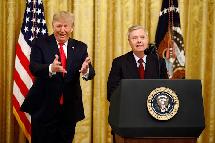 President Donald Trump gestures as Sen. Lindsey Graham, R-S.C., speaks about an upcoming afternoon vote in the Senate during an event in the East Room of the White House about Trump's judicial appointments, Nov. 6, 2019, in Washington.