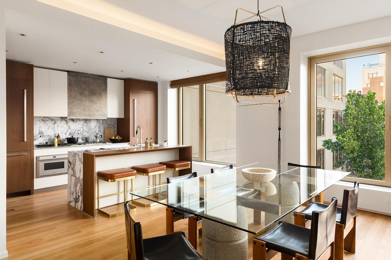 """<div class=""""caption""""> The open-plan kitchen and dining room is grounded by oak wood and accented in black and white. The stools at the oak bar are by Kravitz Design for CB2. A black pendant by Ay Illuminate hangs over the Giovanni Offredi for Saporiti dining table with chairs by Tobia and Afra Scarpa for Molteni. Kitchen appliances by Gaggenau. </div>"""