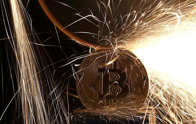 Sparks glow around a commemorative bitcoin (real bitcoins are not tangible) in this illustration. REUTERS/Dado Ruvic