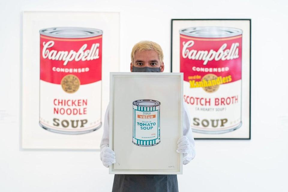 A Christie's employee holds Soup Can – White/Emerald/Tan by Banksy (Dominic Lipinski/PA) (PA Wire)