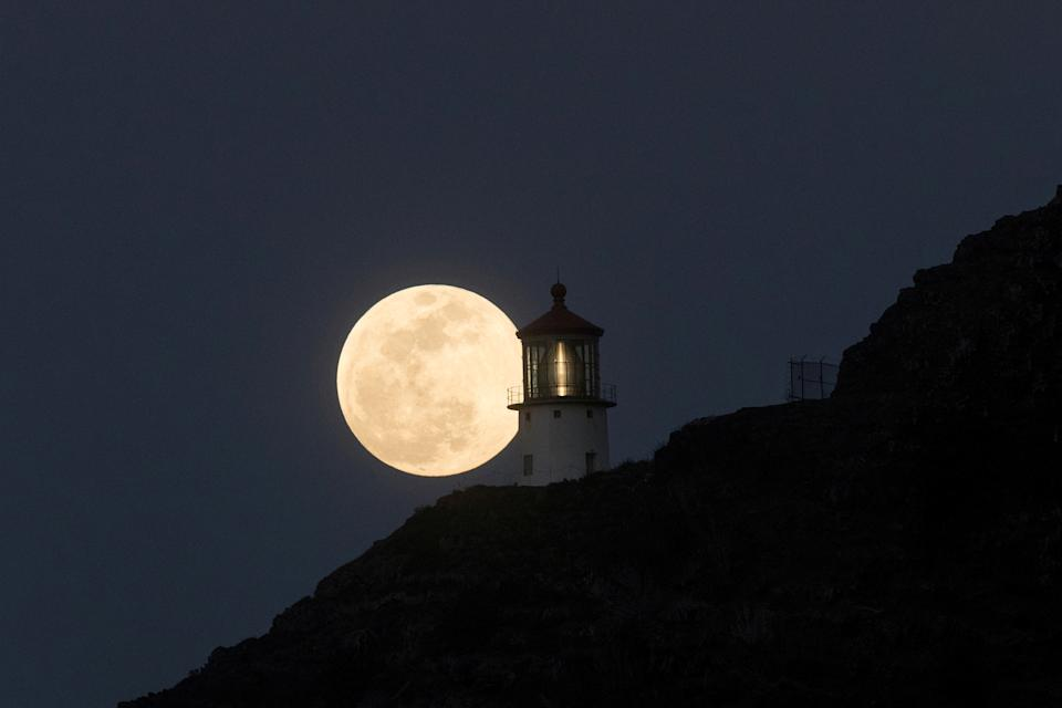 <p>A Super Flower Moon rises over the Makapuu lighthouse in east Oahu, Honolulu, Hawaii, U.S., May 25, 2021. Picture taken May 25, 2021. REUTERS/Marco Garcia TPX IMAGES OF THE DAY</p>