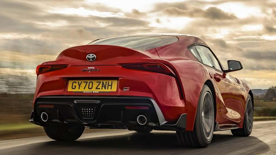 A red Toyota Supra drives away from the camera