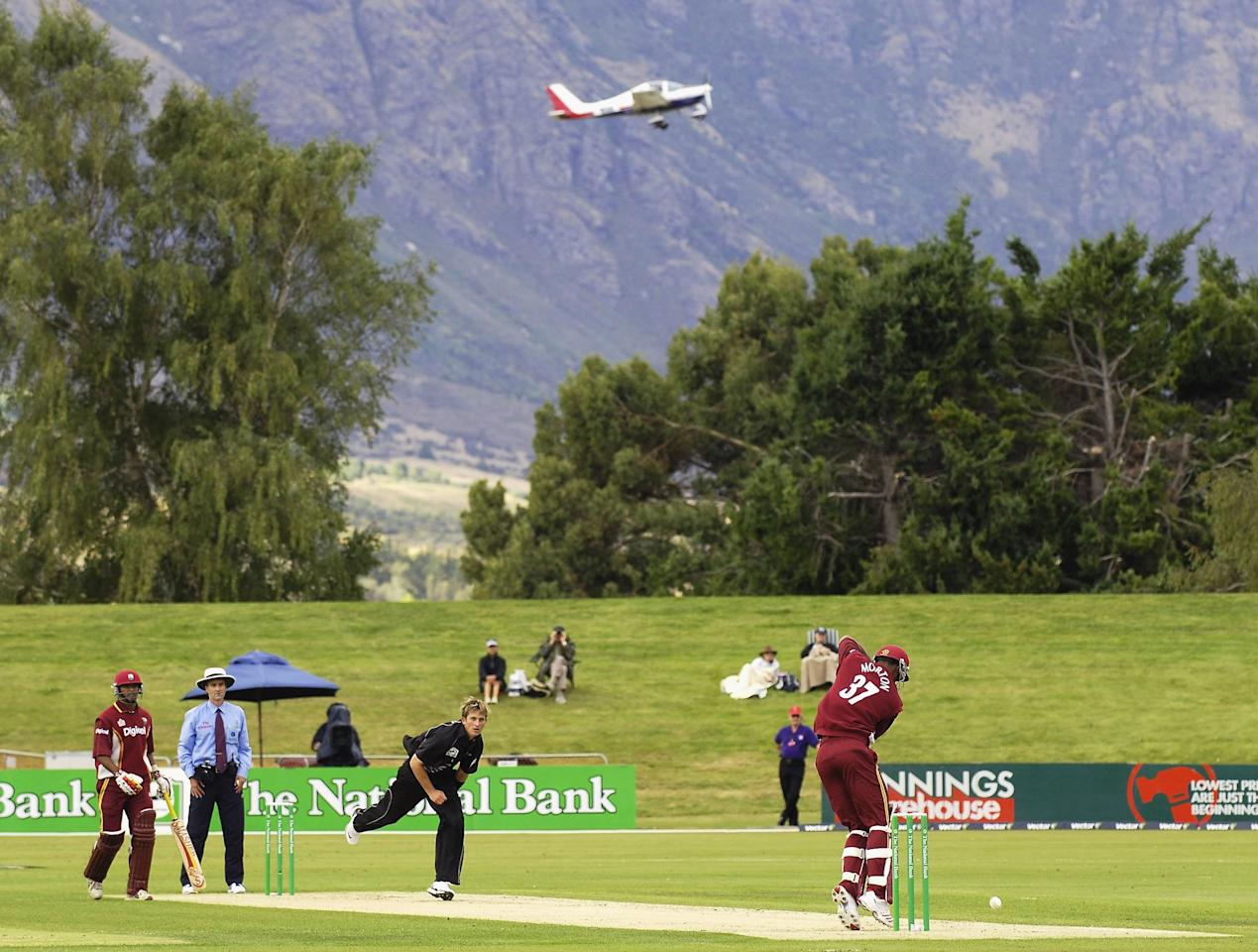 QUEENSTOWN, NEW ZEALAND - FEBRUARY 22:  An aircraft flies past players during the second one day international cricket match between New Zealand and the West Indies at the Queenstown Event Centre, February 22, 2006 in Queenstown, New Zealand.     (Photo by Michael Thomas/Getty Images)