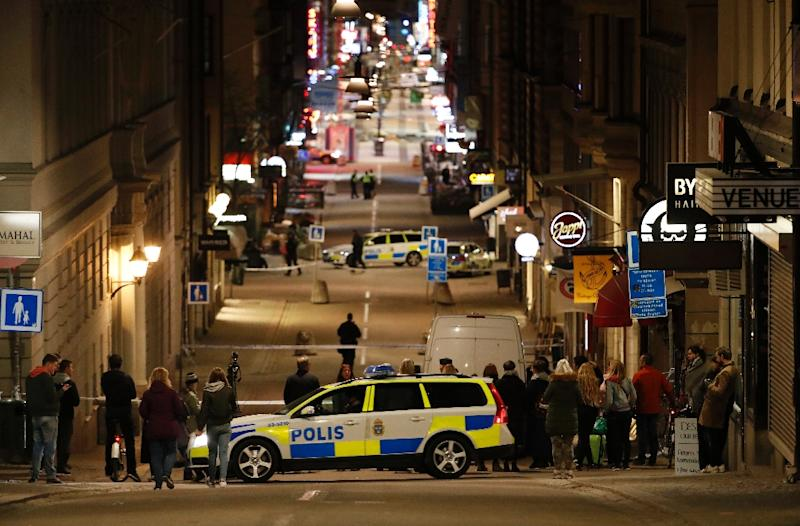 People stand behind a cordon as police work at the scene of a truck attack that killed four people outside a busy department store in central Stockholm on April 7, 2017 (AFP Photo/Odd ANDERSEN)
