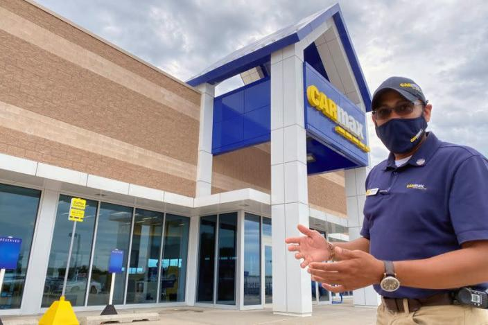 """Brandon Parrum, general manager of CarMax's Des Moines store, shows where customers who arrange to buy a car on line can come for """"contactless"""" curbside pickup"""