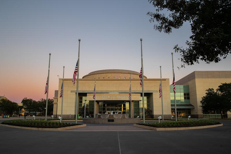 Flags flying at half-staff are seen at the entrance of the George Bush Presidential Library during sunset in College Station, Texas, on Dec. 1, 2018. (Photo: SUZANNE CORDEIRO via Getty Images)