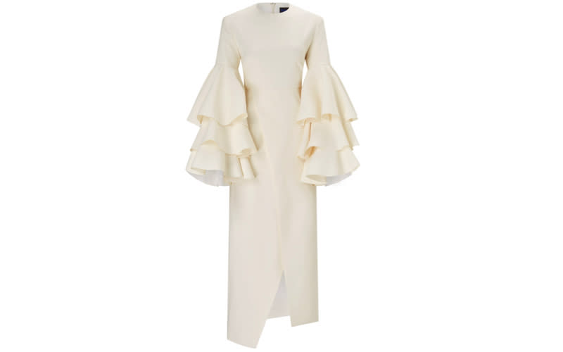 """<p>For those willing to venture outside of their sartorial comfort zone, may we recommend gram-worthy ruffle sleeves. With an elegant bodice and a high fashion kick-split, you won't believe the price tag. <a rel=""""nofollow noopener"""" href=""""https://www.solacelondon.com/minelli-dress-cream-7583.html"""" target=""""_blank"""" data-ylk=""""slk:Shop now"""" class=""""link rapid-noclick-resp""""><em>Shop now</em></a>. </p>"""