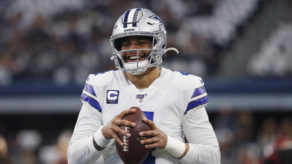 Dak Prescott smiles while holding a football.