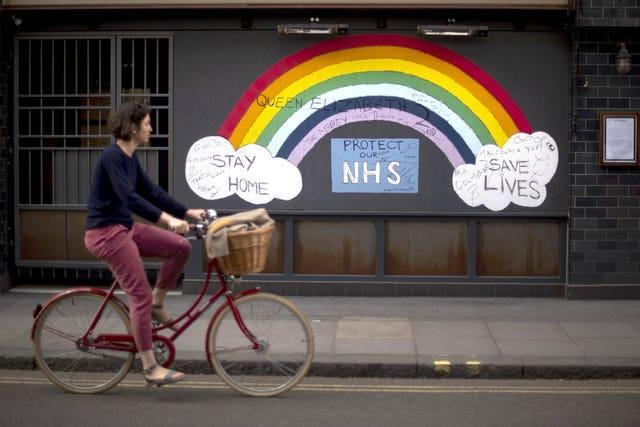 A woman cycling past a rainbow graffiti in support of the NHS in Soho, central London (Victoria Jones/PA)