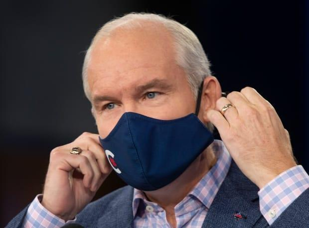 Conservative Leader Erin O'Toole removes his mask before speaking to the media Tuesday, August 24, 2021 in Ottawa. Canadians will vote in a federal election on Sept. 20. (Ryan Remiorz/Canadian Press - image credit)