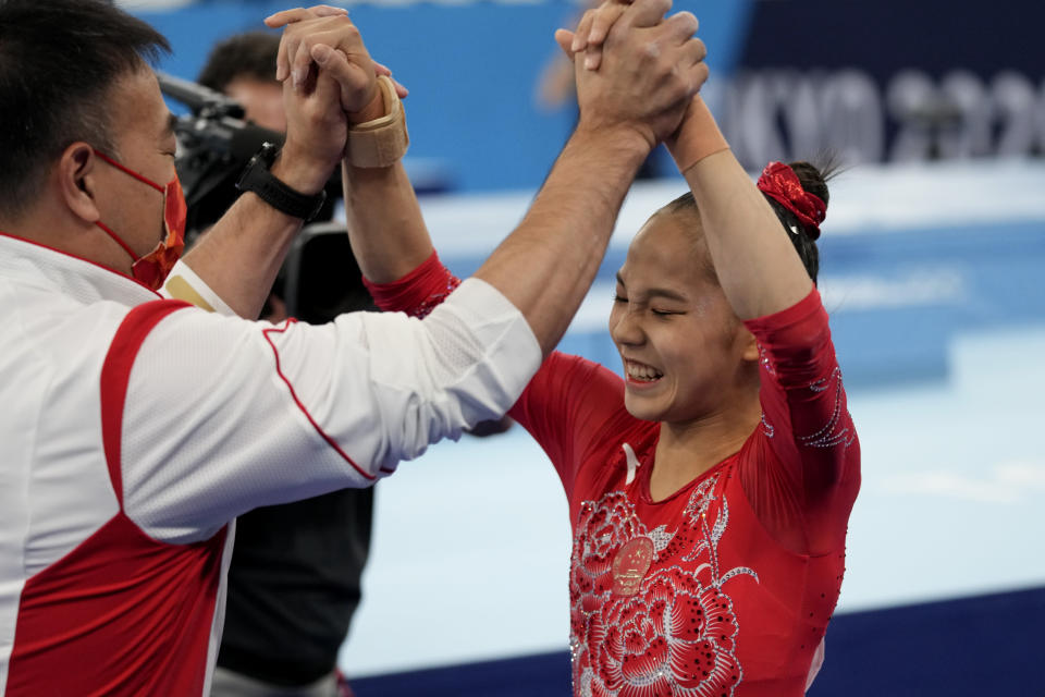 Tang Xijing, of China, celebrates with her coach after performing on the balance beam during the artistic gymnastics women's apparatus final at the 2020 Summer Olympics, Tuesday, Aug. 3, 2021, in Tokyo, Japan. (AP Photo/Ashley Landis)