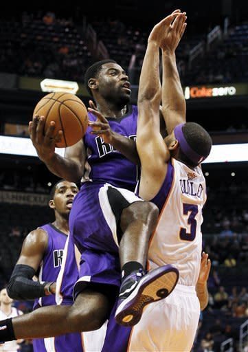 Sacramento Kings' Tyreke Evans tries to drive around Phoenix Suns' Jared Dudley (3) as Kings' Jason Thompson, back left, looks on during the first half of an NBA preseason basketball game, Monday, Oct. 22, 2012, in Phoenix. (AP Photo/Ross D. Franklin)
