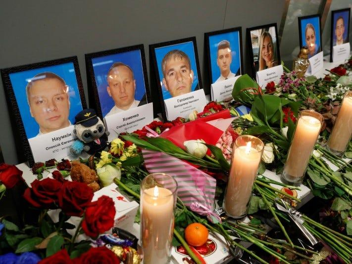 FILE PHOTO: Flowers and candles are placed in front of the portraits of the flight crew members of the Ukraine International Airlines plane that was shot down by Iran, at a memorial at the Boryspil International airport outside Kiev, Ukraine January 11, 2020. REUTERS/Valentyn Ogirenko