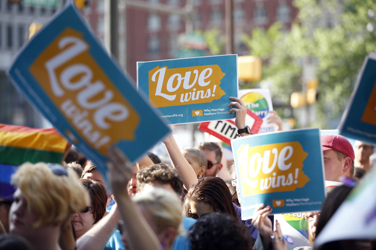People hold up signs and cheer during a rally at City Hall, Tuesday, May 20, 2014, in Philadelphia. Pennsylvania's ban on gay marriage was overturned by a federal judge Tuesday. (AP Photo/Matt Slocum)