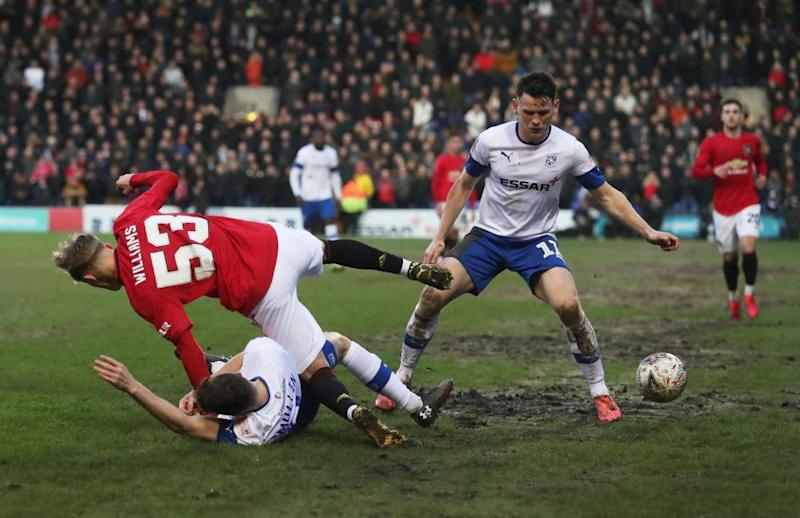 Manchester United's Brandon Williams takes a tumble in the mud at Prenton Park