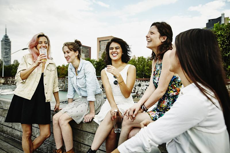 Laughing group of female friends having drinks together on rooftop deck