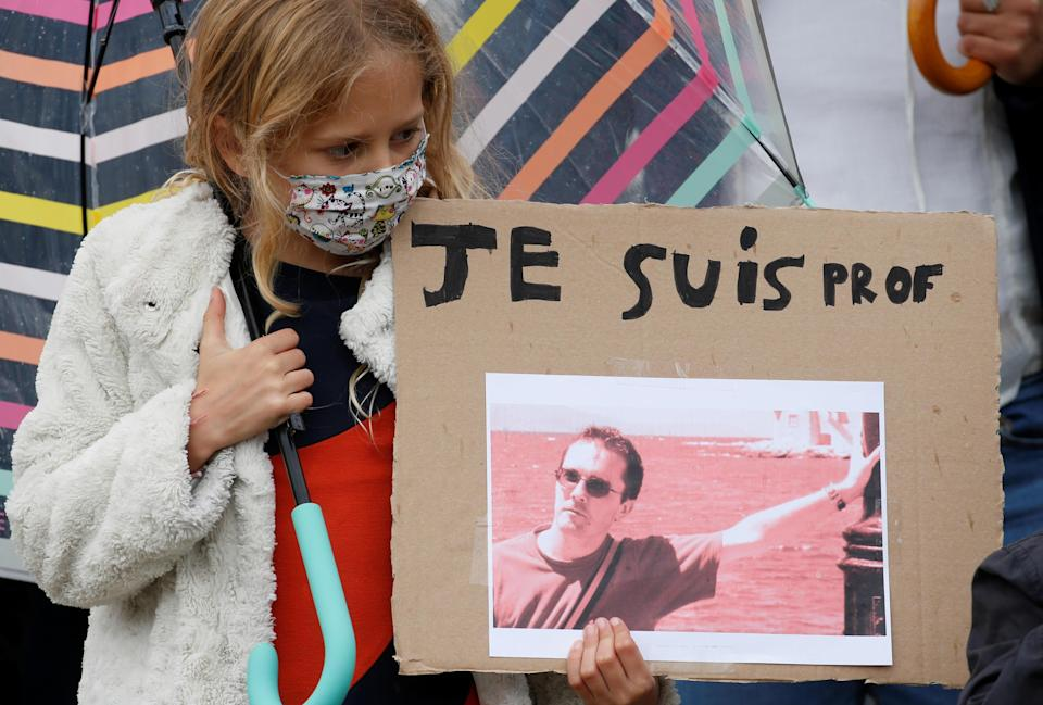 A girl holds a banner with a picture of Samuel Paty, the French teacher who was beheaded on the streets of the Paris suburb of Conflans St Honorine, during a tribute at the Place de la Republique, in Lille, France, October 18, 2020. / Credit: PASCAL ROSSIGNOL / REUTERS