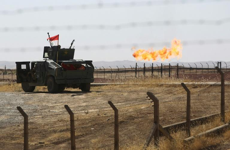An Iraqi army vehicle stands guard at the Bai Hassan oil field, west of Kirkuk, on October 17, 2017, one of a string retaken from the Kurds this month in a crippling blow to their finances