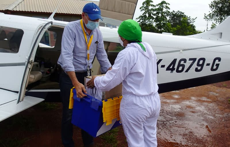 Bacteriologist Diana Carolina Galvan from the Hospital de La Primavera using protection elements gives to the pilot Ernesto Perez a box with samples of the coronavirus disease (COVID-19) that will be processed in Bogota, in La Primavera