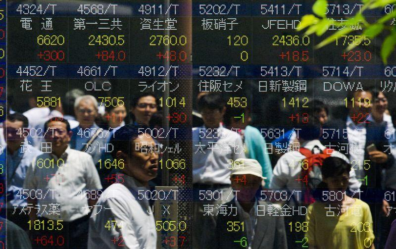 People are reflected in board displaying stock indices in Tokyo