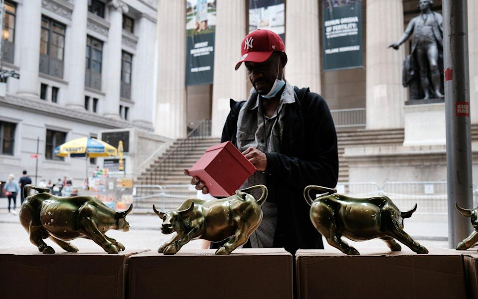 A vendor sells replicas of the Wall Street Bull outside of the New York Stock Exchange - Spencer Platt/Getty Images North America