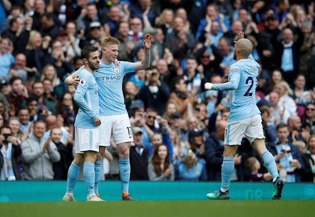 """Soccer Football - Premier League - Manchester City v Swansea City - Etihad Stadium, Manchester, Britain - April 22, 2018 Manchester City's Kevin De Bruyne celebrates scoring their third goal with Bernardo Silva and David Silva REUTERS/Phil Noble EDITORIAL USE ONLY. No use with unauthorized audio, video, data, fixture lists, club/league logos or """"live"""" services. Online in-match use limited to 75 images, no video emulation. No use in betting, games or single club/league/player publications. Please contact your account representative for further details."""