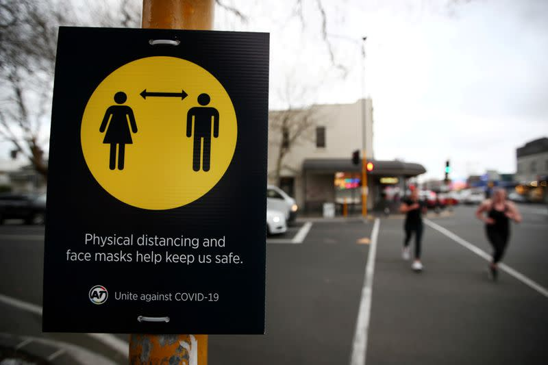 FILE PHOTO: People jog past a social distancing sign in Auckland, New Zealand, August 31, 2020