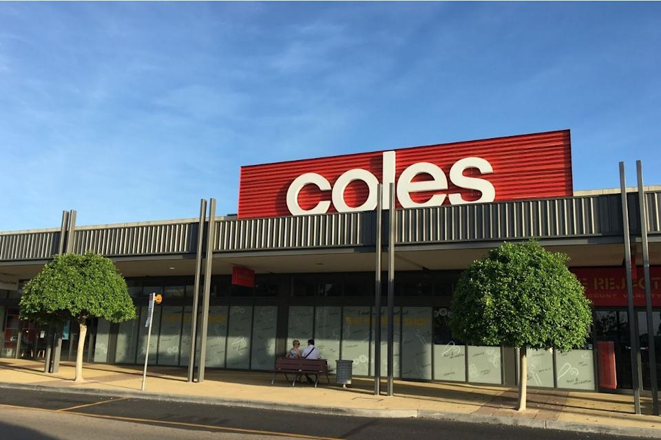 Two people sit outside Coles on a bench. Source: Getty Images