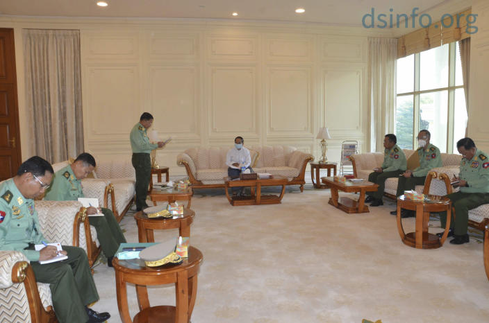 In this photo released by The Military True News Information Team, Myanmar Acting President Myint Swe, center, military chief Senior Gen. Min Aung Hlaing, standing at left, and other military members of National Defence and Security Council attend a meeting at Presidential Palace in Naypyitaw, Myanmar Monday, Feb. 1, 2021. (The Military True News Information Team via AP)