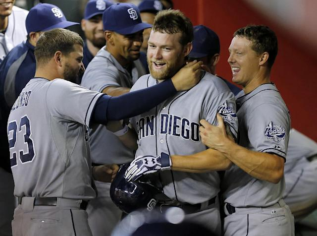 San Diego Padres players grab pitcher Andrew Cashner in the dugout, after first ignoring him, following his solo home run during the sixth inning of a baseball game against the Arizona Diamondbacks, Saturday, July 27, 2013, in Phoenix. (AP Photo/Matt York)