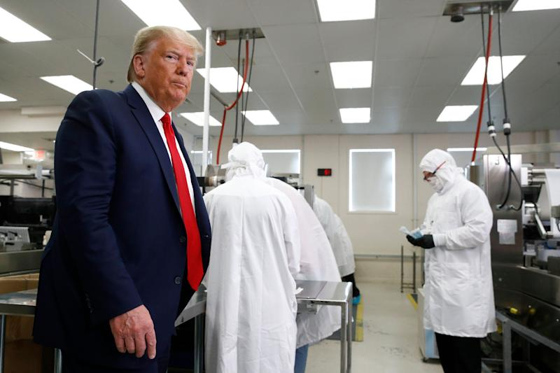 President Donald Trump roams the factory floor at Puritan Medical Products in Guilford, Maine, around suited-up employees working with sterile COVID-19 testing swabs. (Photo: ASSOCIATED PRESS)