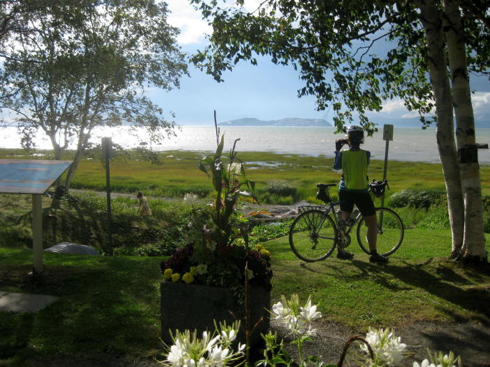 FILE - A cyclist takes in the St. Lawrence vista at Notre-Dame-du-Portage, Quebec, on Aug. 12, 2015. Along the south shore of the St. Lawrence River in this area of around Kamouraska, the panorama of river, sky, flowers and gardens defines the magic of bicycling the Route Verte network in Quebec. (AP Photo/Cal Woodward, File)