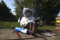 Beekeeper Samantha Jones prepares a bee smoker near hives kept near Iola, Wis., on Wednesday, Sept. 23, 2020. Among other things, the smoke helps calm the bees so beekeepers can open the hives. Jones and her husband, James Cook, have worked with honey bees for several years but started their own business this year — and proceeded with plans even after the coronavirus pandemic hit. (AP Photo/Carrie Antlfinger)