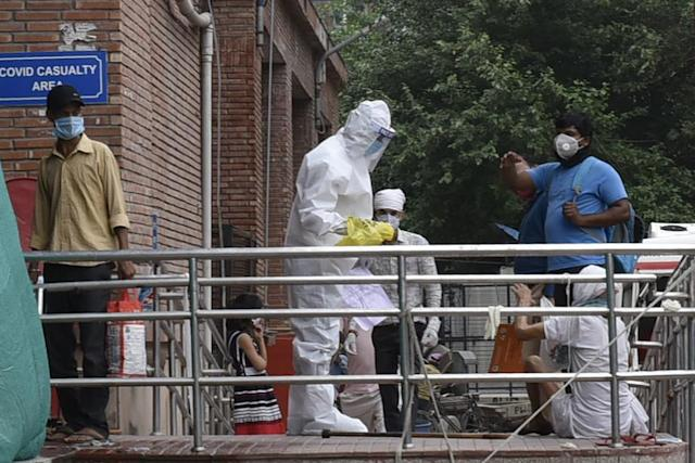 A medical worker in PPE gear attends to people outside the COVID-19 ward at the Lok Nayak Jai Prakash in New Delhi. (Photo by Vipin Kumar/Hindustan Times via Getty Images)