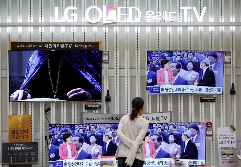 FILE PHOTO: A woman looks at LG Electronics' organic light-emitting diode (OLED) TV sets, which are made with LG Display flat screens, at its store in Seoul, South Korea, April 26, 2016. REUTERS/Kim Hong-Ji/File Photo