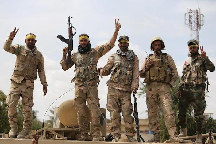 Shiite fighters from the Popular Mobilisation units flash the sign for victory in Tikrit on April 1, 2015 (AFP Photo/Ahmad Al-Rubaye)