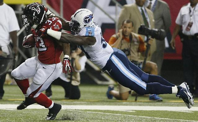 Atlanta Falcons running back Devonta Freeman (33) moves the ball against Tennessee Titans middle linebacker Moise Fokou (53) during the second half of an NFL preseason football game, Saturday, Aug. 23, 2014, in Atlanta. (AP Photo/John Bazemore)